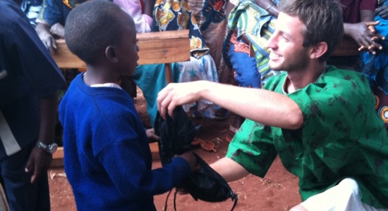 SDSU public health student hands out a backpacks to local children in Kongwa.