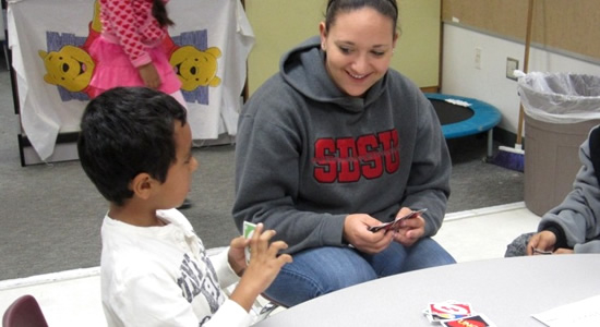 Student Playing Uno with Children