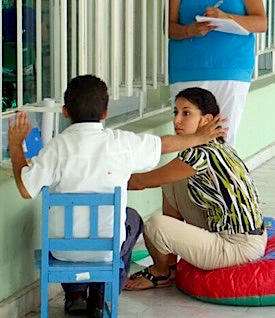 Photo: boy in chair talking with teacher