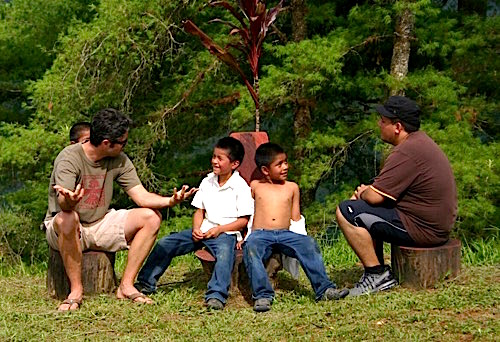 Photo: SDSU teacher scholars visit with young boys outdoors under trees