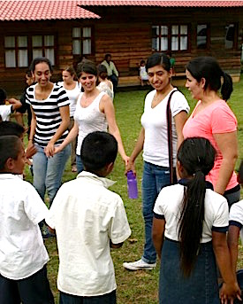 Photo: Teacher scholars hold hands with children in outdoor circie