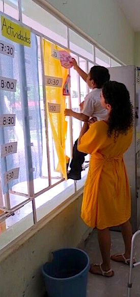 Photo: Teacher holds up small boy to post work in classroom  window