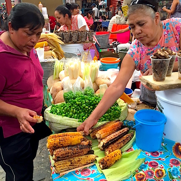Photo: Women at market with grilled corn for sale