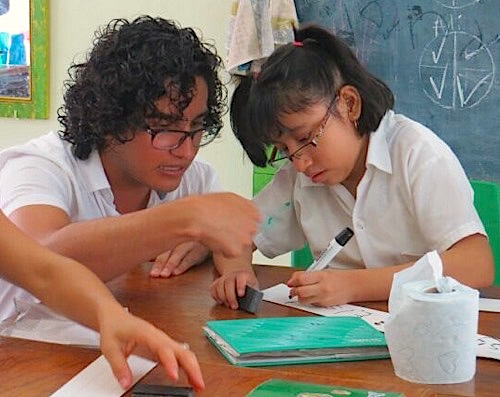 Photo: Young girl getting help from teacher scholar in classroom