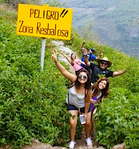 Photo: Student group hiking on mountainside with sign Peligro Zona Resbalosa