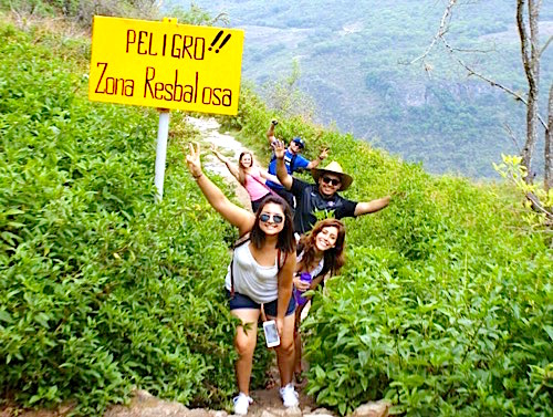 Photo: Hiking group passes sign on mountain path reading peligro Zona Resbalosa