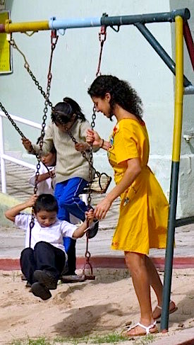Photo: Teacher scholar with kids on outdoor swing set