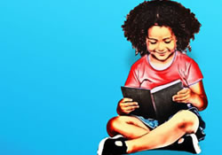 young girl sitting on the floor reading a book
