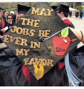 Graduate in decorated cap that says May the Jobs be Ever in My Favor