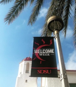 Photo: Palm tree, campus building, and signage saying Welcome Week SDSU