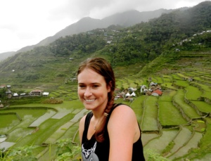 Photo: Study abroad student posing before cultivated mountainous scene