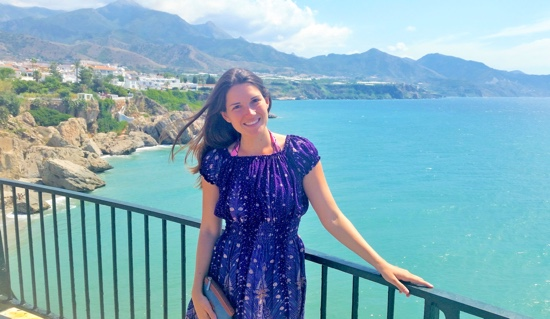 Photo: Caitlin Roth posing on balcony overlooking Mediterranean Sea