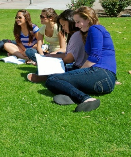 Photo: students with notebooks seated on grass