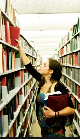Photo: Student in the stacks reaching for a library book