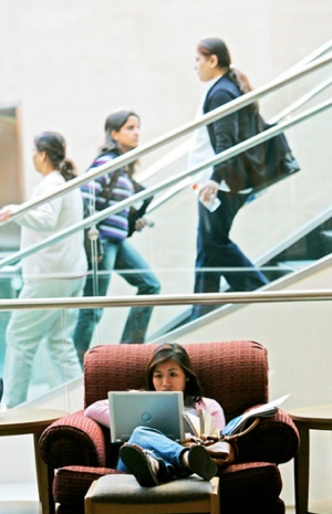 Photo: students going up and down library stairs, one student reading in a chair