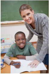 Photo: Elementary school child at desk with teacher and open book
