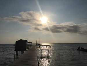Photo: sun shining through clouds over pier and ocean