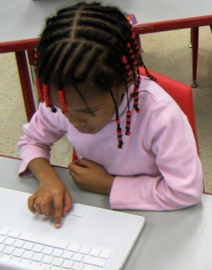 Girl with braids working with laptop computer