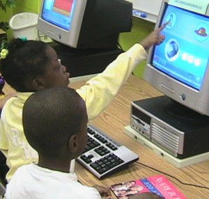 Girl pointing to computer screen with boy watching