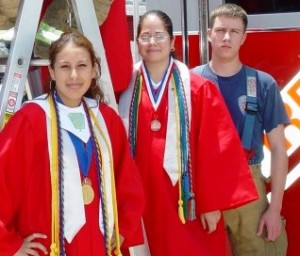 Two girls in graduation robes and one boy in EMT gear