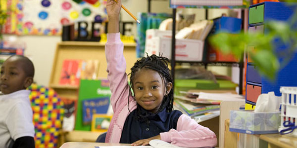 Young student raising hand in class