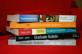 Stack of SDSU Graduate Bulletins from various years