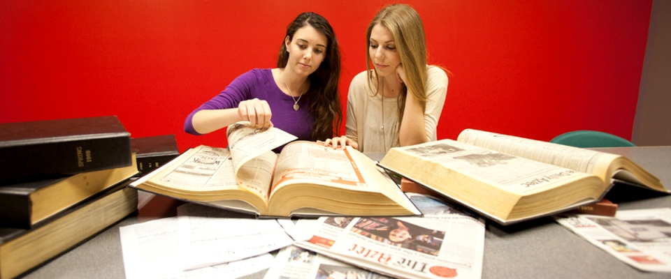 Tara Millspaugh and Paige Nelson review old issues of The Daily Aztec.