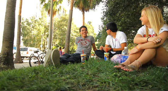 Three students sit outside of Tenochca Residence Hall.