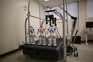 Photo of 3 small robots and a large 4-legged robot