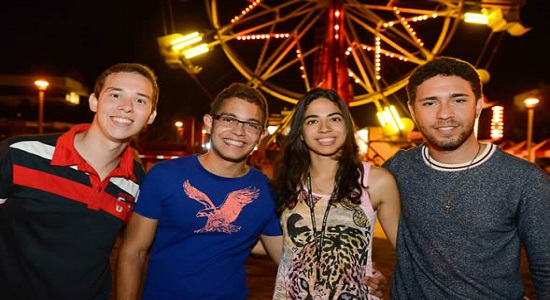 Four students smiling and posing for a picture in front of a ferris wheel at night.