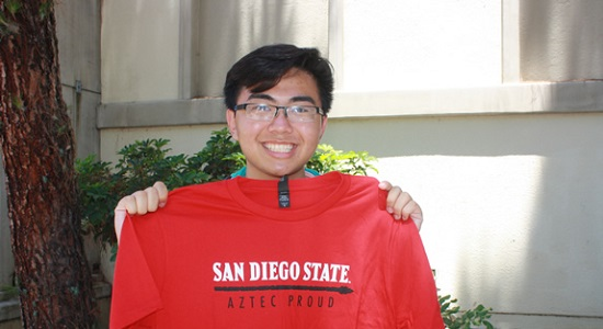 Incoming freshman Tri Nguyen smiles and holds up a red shirt that says