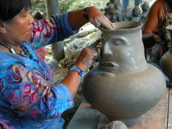 A woman in an Ecuadorian village sculpts a ceremonial vase.
