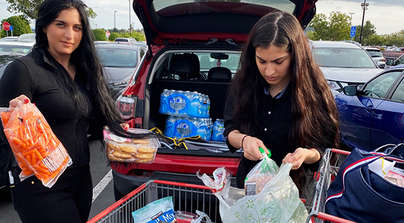 Loading groceries in their car for homebound community members are Milano Sliwa (left), and her sister Monica Sliwa (right).