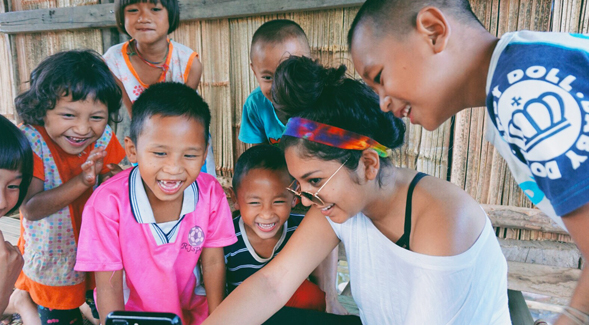 SDSU student Nicole Garcia playing with children while volunteering abroad.