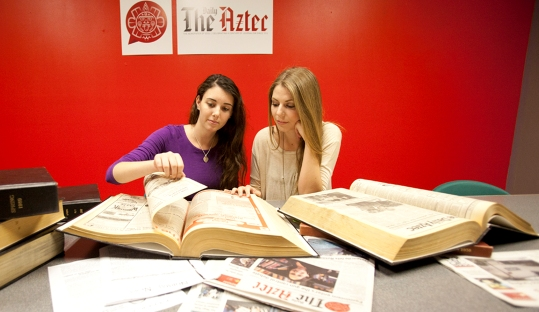 The Daily Aztec News Editor Tara Millspaugh and Photo Editor Paige Nelson review old issues of the paper. (Photo by Antonio Zaragoza)