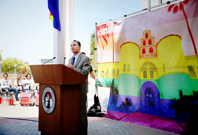 SDSU President Elliot Hirshman in front of the Rainbow Flag