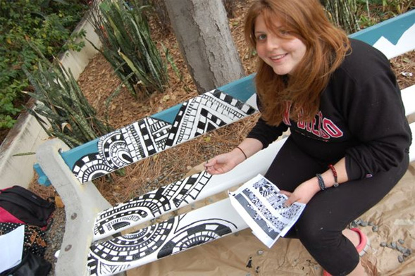 A student paints her design on one of the 19 benches chosen for beautification.