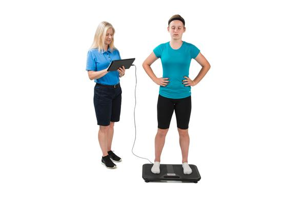A trainer tests an athlete's balance on the BTrackS balance board.