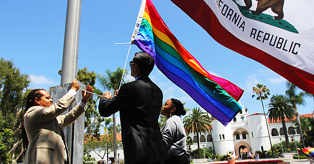 From left, Aaron Bruce, Cody Barbo and Channelle McNutt raise the rainbow flag.  Photo by Antonio Zaragoza.