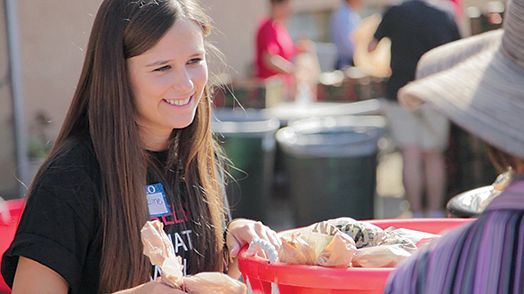 Associated Students Morale Commissioner Jacqueline Karczewski gives food to San Diego families in need.