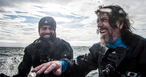 Upon reaching safety on board the zodiac, Steven Quistad, left, and Forest Rohwer breathe a sigh of relief after a close call while diving in Franz Josef Land, Russia. Photo by Andrew Mann/NatGeo