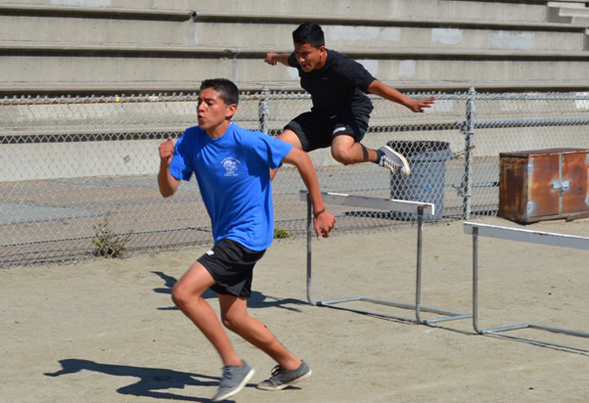 Hilltop High students sprint towards the finish in a hurdle race.