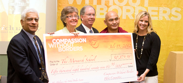 Lama Tenzin Dhonden, SDSU Provost Nancy Marlin and other local university representatives present a check to the Monarch School.