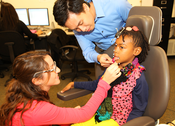 Professor Ignatius Nip and a student assistant prepare a child participant for motion capture speech-language testing.