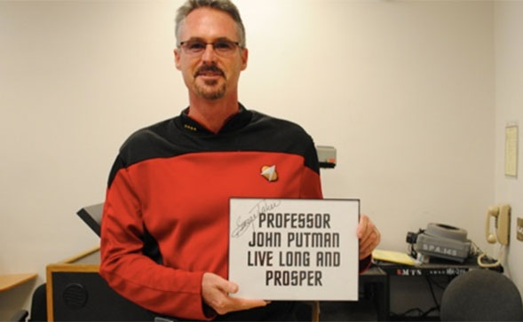 Professor Putman holding a signed card from George Takei i who played Lt. Sulu in the original Star Trek series.