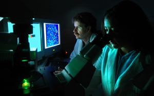 Mark Sussman (far left) looks at a computer screen as a research assistant examines a specimen.