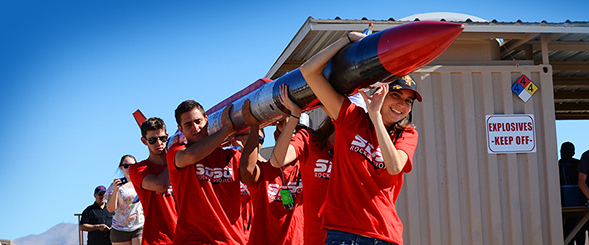 Project members carry the 18-foot rocket to the launchpad. Photo by Daniel Silva