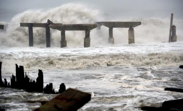 Waves crash against a previously damaged pier before landfall of Hurricane Sandy in Atlantic City, N.J. Photo by: Stan Honda