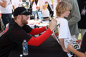 Stephen Strasburg (left) signs a young fan's T-shirt during the event.