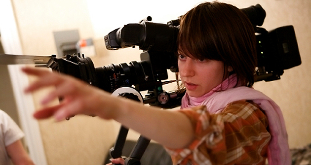 A young woman directs actors during filming.